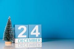 伊芙圣诞节 12月24日 天24 12月月,与一点圣诞树的日历在蓝色背景 冬天 免版税库存照片