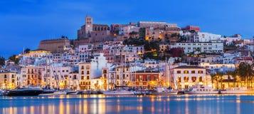 伊维萨岛Dalt维拉街市在与光反射的晚上在水,伊维萨岛,西班牙中 库存照片