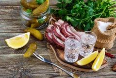 伏特加酒两个小玻璃与柠檬切片、酱瓜和黑麦面包的用在黑暗的背景的盐味的烟肉 免版税库存图片