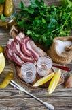 伏特加酒两个小玻璃与柠檬切片、酱瓜和黑麦面包的用在黑暗的背景的盐味的烟肉 免版税图库摄影