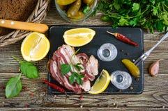 伏特加酒两个小玻璃与柠檬切片、酱瓜和黑麦面包的用在黑暗的背景的盐味的烟肉 免版税库存照片