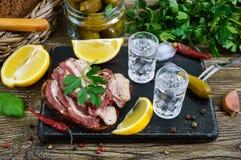 伏特加酒两个小玻璃与柠檬切片、酱瓜和黑麦面包的用在黑暗的背景的盐味的烟肉 图库摄影
