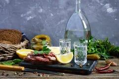 伏特加酒两个小玻璃与柠檬切片、酱瓜和黑麦面包的用盐味的烟肉 图库摄影