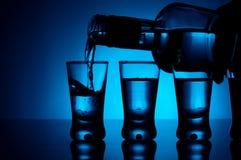伏特加酒涌入与玻璃的一块玻璃点燃了与蓝色背后照明 免版税库存照片