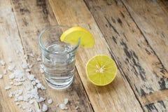 伏特加酒用在木背景的柠檬 免版税库存照片