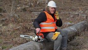 伐木工人坐树在锯附近和谈话在手机 影视素材