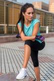 休假的年轻人适合的妇女在行使或跑以后 站立和基于户外城市街道的健身女孩 免版税库存照片