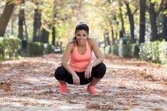 休假的赛跑者运动服的可爱的体育妇女疲倦了微笑愉快和快乐在连续锻炼以后 免版税库存图片