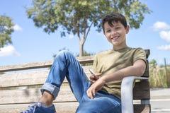 休假的长凳的微笑男小学生使用机动性 免版税库存图片