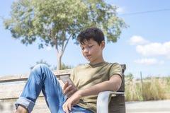 休假的长凳的男小学生使用机动性 免版税库存图片