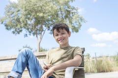 休假的长凳的男小学生使用机动性 库存图片