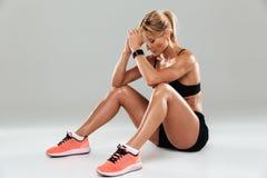 休息一个年轻疲乏的女运动员的画象,当坐时 库存照片