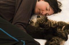 休息与在床上的三只逗人喜爱的小猫的年轻深色的妇女 免版税库存照片