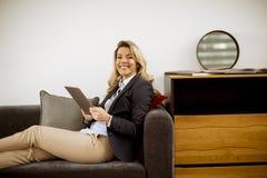 休息与在现代沙发的片剂的年轻女实业家 库存图片