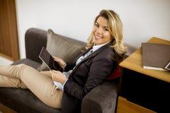休息与在现代沙发的片剂的年轻女实业家 库存照片