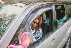 休息与她的在开窗口汽车的腿的妇女 库存照片