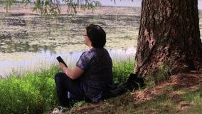 休息与电话的女孩由湖 股票视频