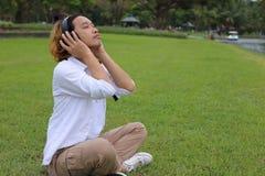 休息与耳机的一个年轻人的画象在公园户外 免版税库存图片