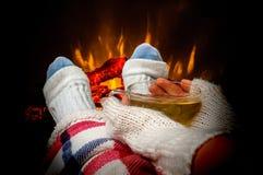 休息与茶的妇女在壁炉附近 免版税库存照片