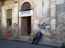 休息他的一个老粉碎的大厦的车间外的棺材制造商在老镇尼科西亚塞浦路斯 免版税库存照片