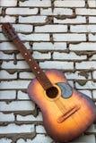 休息反对白色砖背景的声学吉他 库存图片