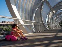 休息和吃在一现代bridg的愉快的妇女赛跑者一个苹果 免版税库存照片