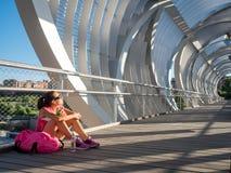 休息和吃在一现代bridg的愉快的妇女赛跑者一个苹果 免版税库存图片