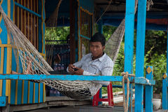 休息和听到音乐的亚裔男孩在他的riv的房子 免版税库存图片