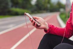 休息和听到音乐的特写镜头母赛跑者在跑步以后 免版税库存图片