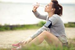 休息和喝被装瓶的水的母慢跑者 免版税图库摄影
