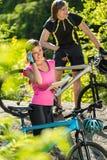 休息和检查路线的骑自行车的人 免版税库存图片