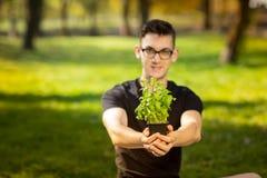 休息在一个公园和舒展手的玻璃的年轻人有罐的蓬蒿在绿色背景 健康生活方式 图库摄影
