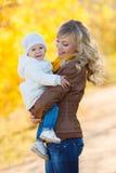 休息在一个公园的妈妈和女儿在秋天 免版税库存照片