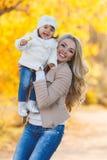 休息在一个公园的妈妈和女儿在秋天 库存图片