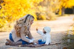 休息在一个公园的妈妈和女儿在秋天 免版税库存图片