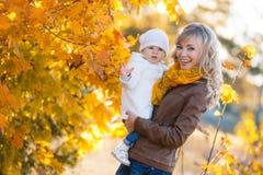 休息在一个公园的妈妈和女儿在秋天 库存照片