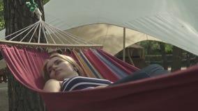 休息在一个吊床的可爱的女孩在公园 影视素材