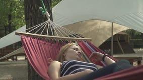 休息在一个吊床的女孩在公园 股票视频