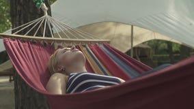 休息在一个吊床的甜女孩在公园 股票视频