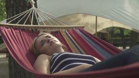 休息在一个吊床的美女在公园 股票录像