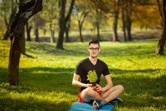休息在一张蓝色席子的一个公园的玻璃的年轻人,在手中拿着新鲜的蓬蒿在绿色背景 健康生活方式 免版税库存图片