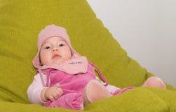 休息在一把绿色椅子的逗人喜爱的小孩婴孩 图库摄影