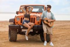 休息在与吉他的海滩的愉快的年轻夫妇 免版税库存照片