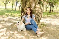 休息在与她的狗的树荫下的可爱的妇女 库存照片