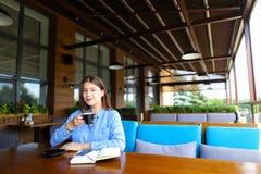 休息在与智能手机、笔记本和咖啡的咖啡馆的女孩 库存图片