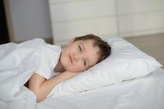 休息在与眼睛的白色床上的小男孩打开 免版税库存图片
