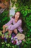 休息在与美丽的花束的象草的丛林的嫩妇女 图库摄影