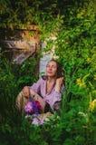 休息在与美丽的花束的象草的丛林的嫩妇女 免版税库存照片