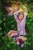 休息在与美丽的花束的象草的丛林的嫩妇女 免版税库存图片