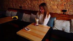 休息在与鸡尾酒的咖啡馆和显示赞许的愉快女孩 影视素材